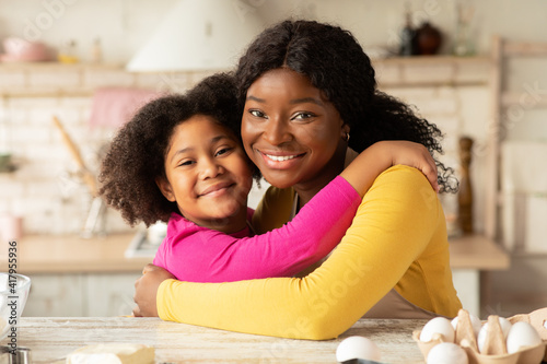 Mother's Day Concept. Portrait Of Black Mom And Daughter Embracing In Kitchen
