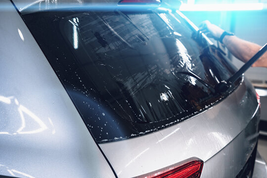 Car window tinting. Process of Installation window tint in Car Detailing Studio Garage by professional detailer, close up.