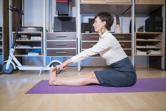 young woman practicing yoga in the office