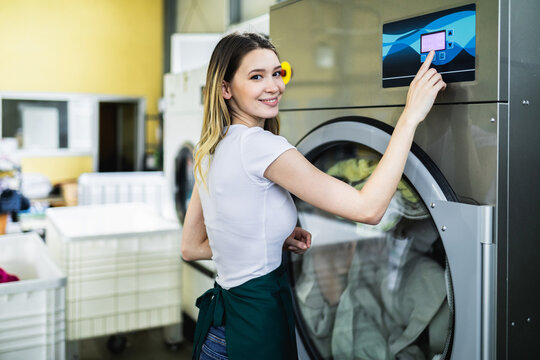 Female worker loads the laundry clothing into the washing machine at the dry cleaners.