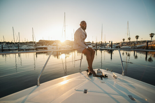 A cheerful elegant mature bald bearded black man in a summer suit consisting of striped shorts and blazer is sitting on the railings of his luxurious yacht, laughing and enjoying the dramatic sunset