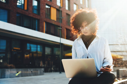 Curly haired woman is working on a laptop sitting on a bench outside in the city