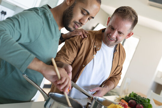 Multi ethnic gay male couple smiling and preparing food together at home