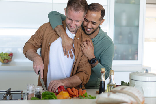 Multi ethnic gay male couple smiling, preparing food and hugging at home