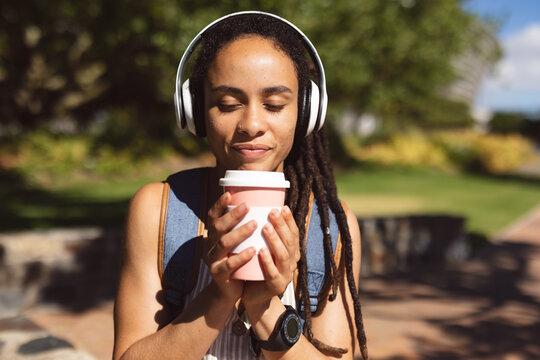 Smiling african american woman wearing headphones sitting drinking coffee in park