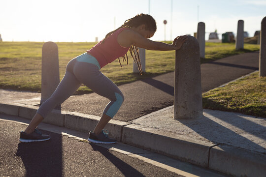 African american woman focusing exercising in park leaning against wall, stretching