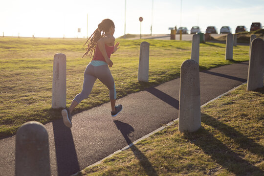 African american woman exercising in park, running on path on sunny day