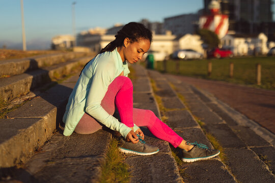 African american woman wearing sports clothes exercising in urban street tying shoe