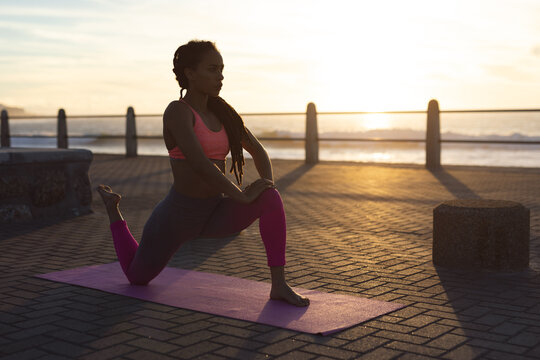 African american woman exercising on promenade by the sea doing yoga