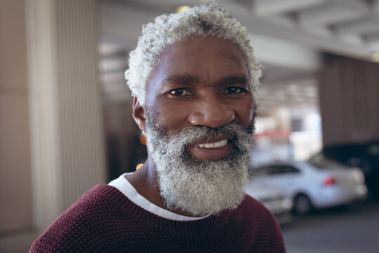Portrait of casually dressed african american senior man with beard smiling in street