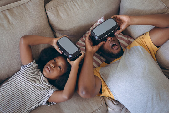 African american man and his daughter lying in living room using vr headset
