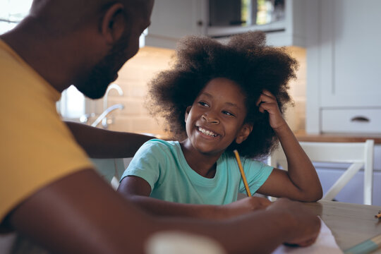 African american girl doing homework with her father