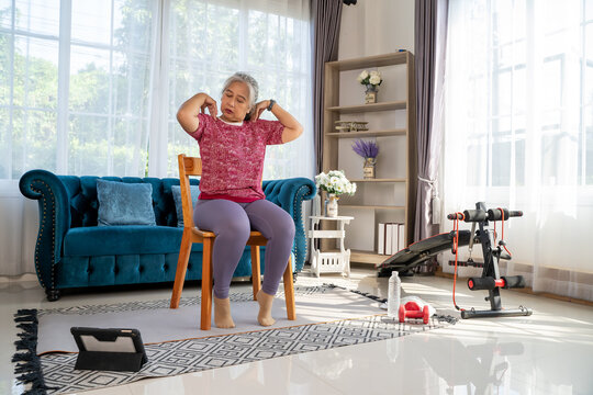 Senior woman slowly rotate both shoulders  for exercise at home