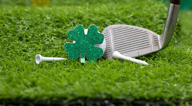 Golf for St. Patrick's Day with shamrock clover on green grass with golf club