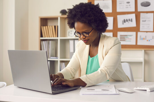 Attractive busy young african american woman sitting at desk in office, working with project report document typing on laptop computer keyboard for recording result or filling digital database