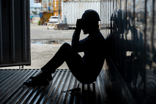 Depressed and tried foreman or businessman sitting inside the container in shipyard logistic factory because losing his job or fired. Worker or officer feeling sad and depressed.