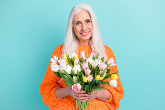 Photo of happy joyful old woman hold hands tulips spring holiday season isolated on pastel teal color background