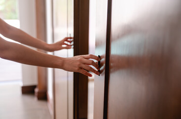 Close up women hand open the door knob or push the wooden door. Wall mural