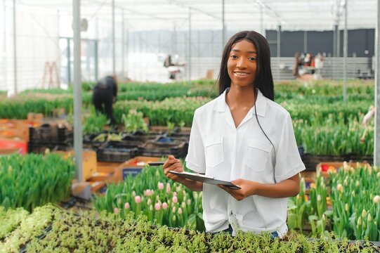 Beautiful young smiling african american girl, worker with flowers in greenhouse. Concept work in the greenhouse, flowers.