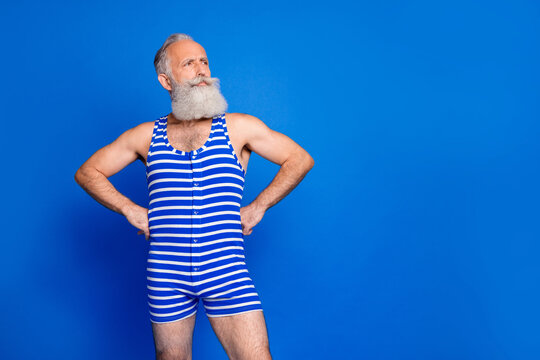 Photo of optimistic grey beard man stand look empty space wear blue swimsuit isolated on bright blue color background