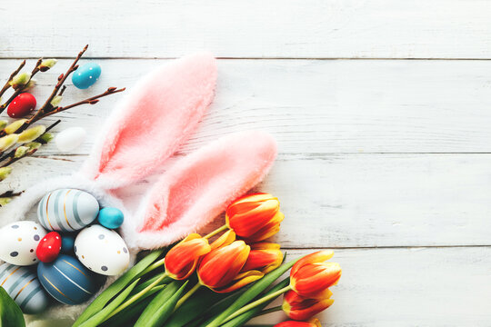 Easter, spring flat lay with colorful eggs, red tulip flowers, bunny ears and willow twigs. Copy space