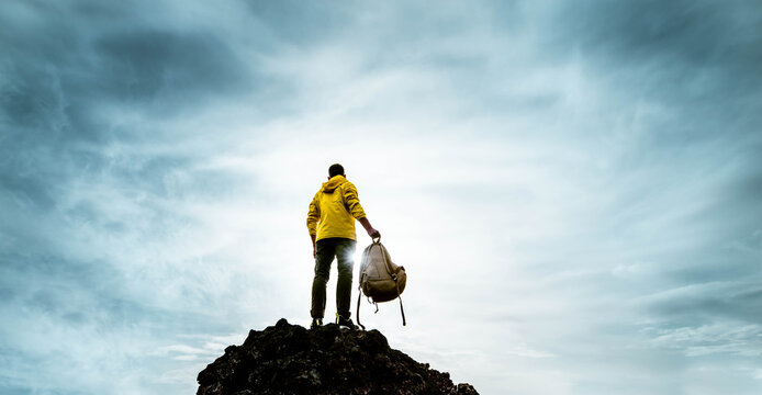Successful man standing on the top of the mountain at sunset - Hiker with backpack extreme climbing - Sport success and inspirational concept