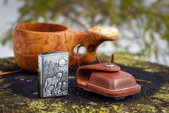 Zippo Timberwolves lighter with a leather case and a wooden kuksa with delicious coffee on an old stump in the spring forest. The background is blurred.