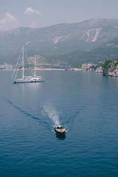 A luxury wooden sports motor boat delivers VIPs from a large white boat docked off the coast of Montenegro, near the island of Sveti Stefan, Budva Riviera.