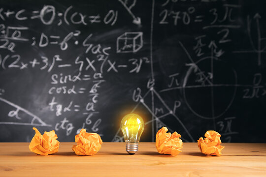 light bulb with papers on blackboard