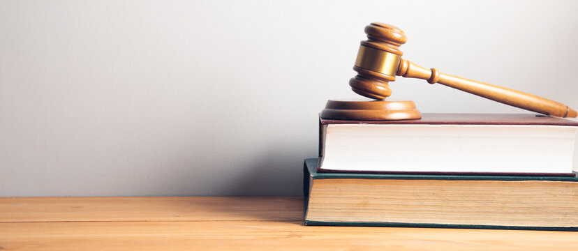 Law concept - law book with a wooden judges gavel
