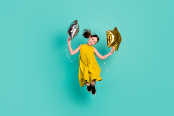 Full size photo of impressed nice brown hair girl hold balloons jump wear yellow dress isolated on bright teal color background Wall mural