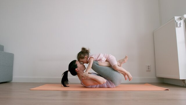 Mother lies on yoga mat and kiss her little baby on her legs