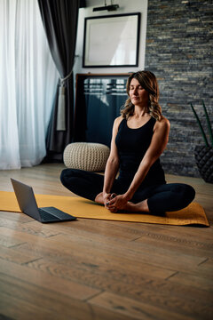 A middle-aged woman doing yoga at home and following video tutorial.