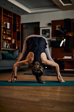 A middle-aged woman doing yoga at home.
