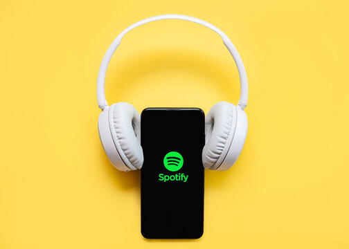 Spotify application icon on black screen of smartphone with white wireless headphone