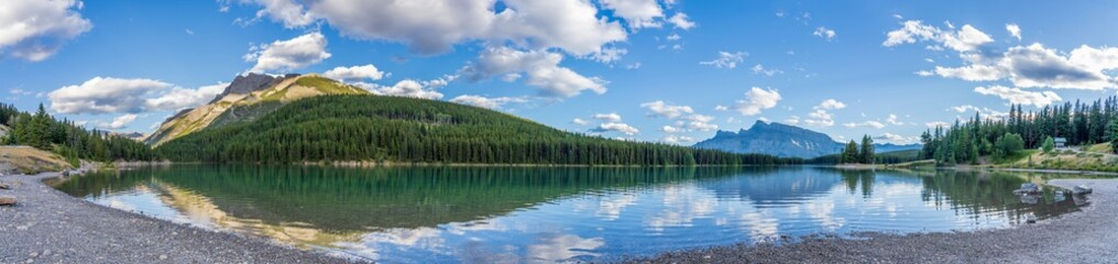 Two Jack Lake panorama view in summer day. Beautiful landscape reflected on water surface. Banff National Park, Canadian Rockies, Alberta, Canada.