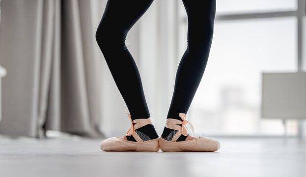 View of ballerina legs staying in first position during dance class in choreography studio