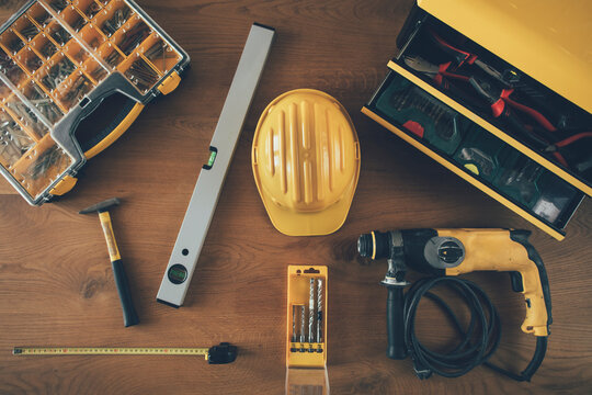 Construction worker equipment. High angle view of helmet, drill machine, level, meter and other tools