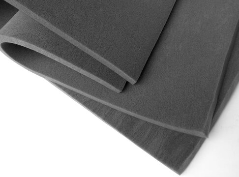 curved folds of two gray industrial sponge foam sheets on a white background.  rubber foam material that is supple, elastic, textured. top view