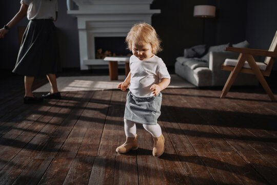 Dancing at home to the music. Cute little blonde girl. The child smiles in a cheerful mood. He plays his own games. Clothing stylish children's dress and shoes.