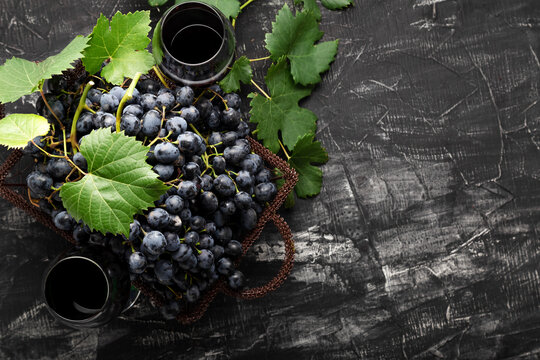 Black grapes basket and glass of red wine on dark rustic concrete background. Flat lay wine composition Red Wine glass or grape juice on black stone table with copy space
