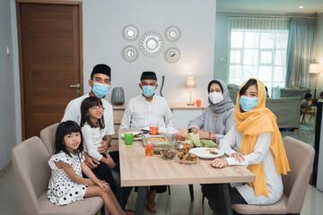 portrait of happy family muslim wear mask during eid mubarak celebration at home