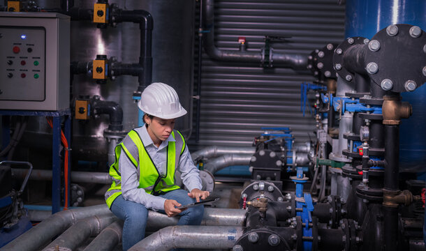 Industry engineer under checking the industry cooling tower air conditioner is water cooling tower air chiller HVAC of large industrial building to control air system.