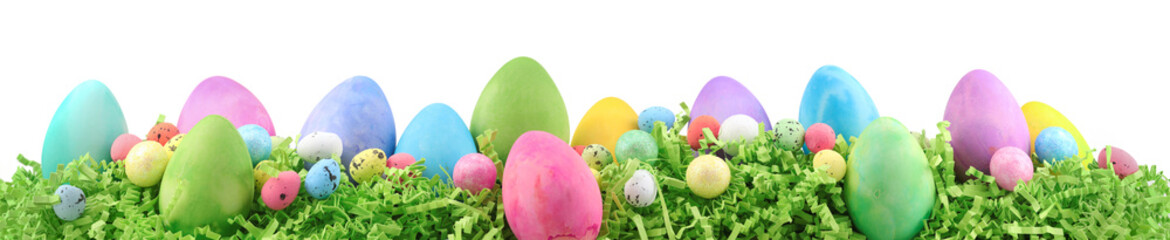 Painted Easter eggs and decorations on arranged on Easter grass. Horizontal banner isolated on...