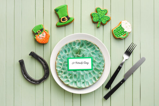 Beautiful table setting for St. Patrick's Day celebration on color wooden background