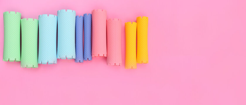 close up of hair curlers on pink background
