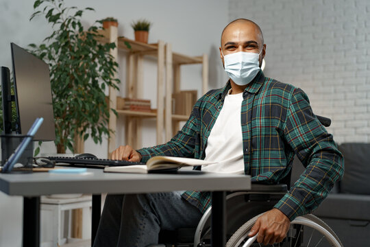 Young disabled man in wheelchair sitting at his working table wearing face mask