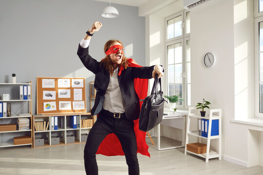Joyful superhero businessperson or corporate employee dancing and fooling around. Funny goofy young office worker in super hero cape and mask having fun at end of work day happy it's time to go home