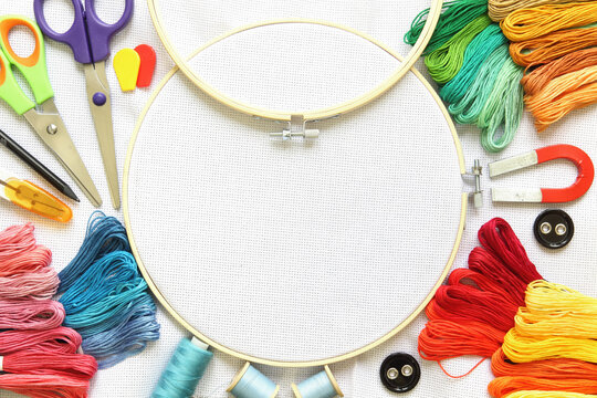 embroidery set with threads and needle, button, scissors and fabric on frame