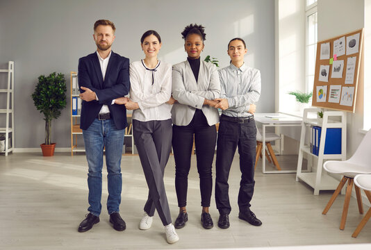 Teamwork, collaboration, partnership concept. Group of smiling mixed race business partners office workers standing and holding crossed hands of each other meaning support unity